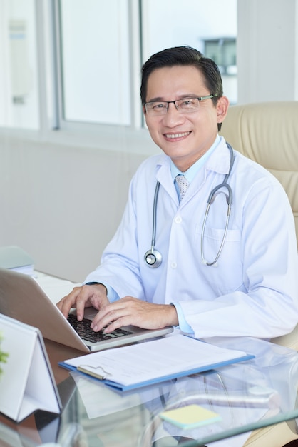 Successful doctor working at office Free Photo