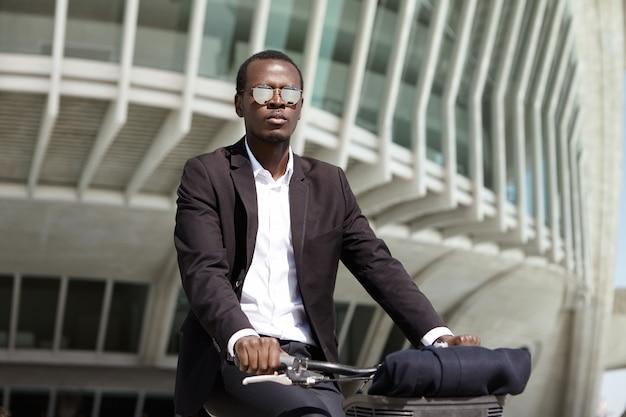環境に配慮しながら空気を汚染する輸送手段や車を選ぶのではなく、自転車でオフィスに行くことを好む、環境に配慮した若いアフロアメリカンの起業家。 無料写真