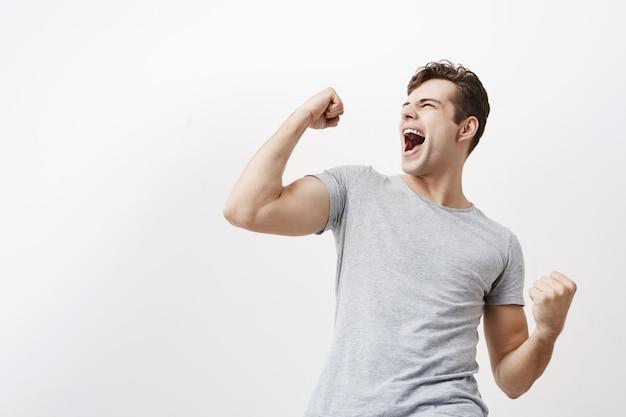 Успешный эмоциональный молодой кавказский мужчина спортсмен с темными волосами кричал да и поднимая сжатые кулаки в воздухе, чувствуя себя взволнованным. люди, успех, триумф, победа, победа и праздник. Бесплатные Фотографии
