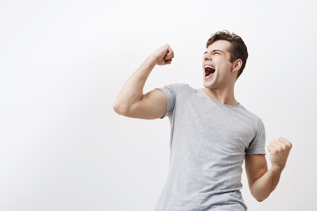 Successful emotional young caucasian male sportsman with dark hair screaming yes and raising clenched fists in the air, feeling excited. people, success, triumph, victory, winning and celebration. Free Photo