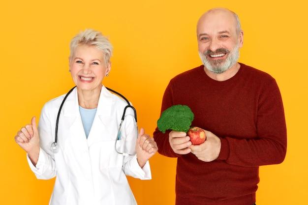 首の周りに聴診器を持ち、興奮した表情をしているエネルギッシュな中年女性医師の成功、彼女の幸せな先輩患者は健康的な食事を選び、ブロッコリーとリンゴを持って、笑顔 無料写真