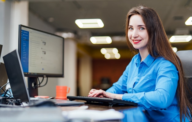 Successful female programmer is sitting at the desk with a computer and works. beautiful woman looking friendly and smiling in a software company office. Premium Photo