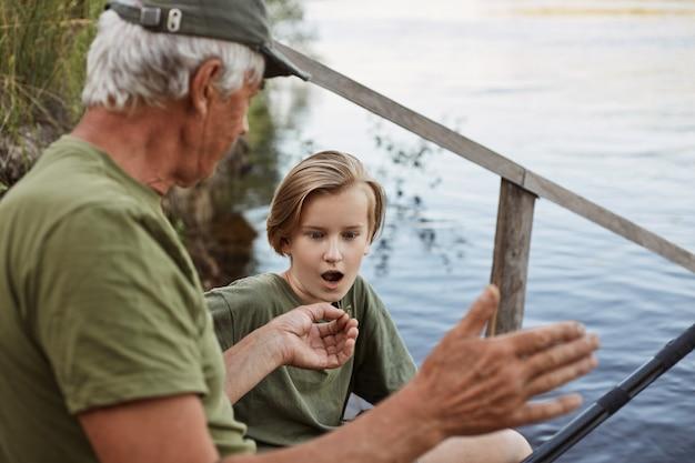 Удачная рыбалка, папа рассказывает о ловле крупной рыбы в летние выходные, ловля рыбы нахлыстом зрелого человека, рыбак с внуком, сын смотрит на отца с раскрытым ртом и удивленным выражением лица Premium Фотографии