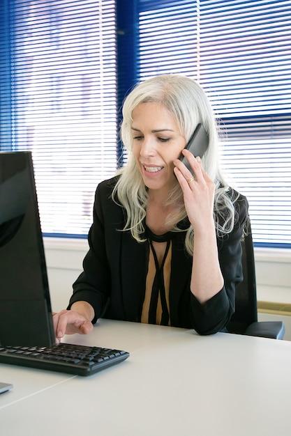 성공적인 회색 머리 여성 Ceo는 핸드폰으로 이야기하고 키보드에 입력합니다. 콘텐츠는 사무실 방에서 일하는 아름다운 사업가를 경험했습니다. 비즈니스, 회사 및 생산성 개념 무료 사진