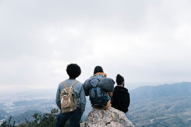 Successful hiker friends enjoy the view on mountain peak Free Photo