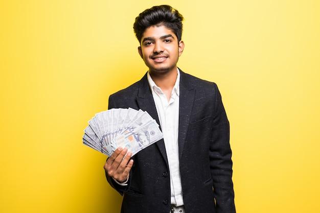 Успешный индийский предприниматель с долларовыми банкнотами в классическом костюме руки смотрит на камеру с зубастой улыбкой, стоя у желтой стены Бесплатные Фотографии