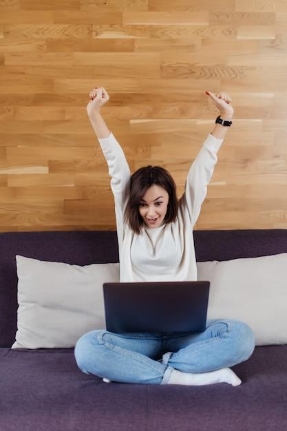 成功した女性は自宅の木製の壁の前に暗いベッドの上に座っているラップトップコンピューターに取り組んでいます 無料写真