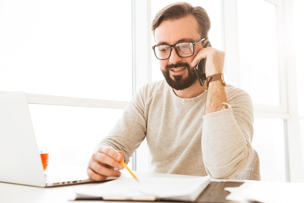 Successful man in eyeglasses running business from home workplace speaking on smartphone, and writing down notes on paper Premium Photo