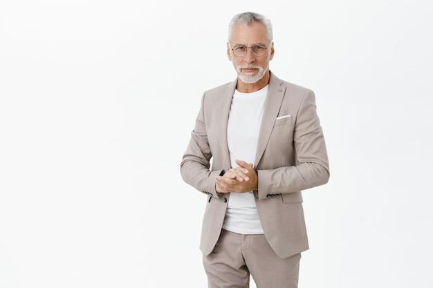 Успешный старый бизнесмен в костюме и очках, выглядящий уверенно Бесплатные Фотографии