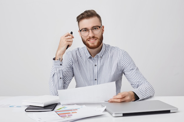Successful professional male enterpreneur holds paper and pen, reads attentively contract Free Photo