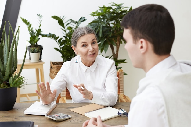 Successful senior woman recruiter in white shirt sitting at her workplace and interviewing unrecognizable man job candidate. two colleague male and female discussing business in modern office Free Photo