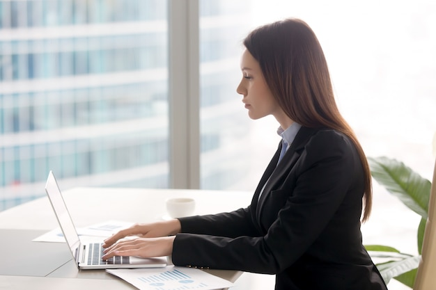 Successful serious business lady working at office desk using laptop Free Photo