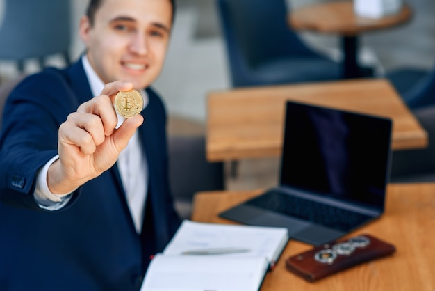 Successful smiling businessman holds a gold bitcoin coin in his hand Premium Photo