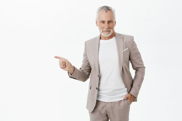左の指を指している成功した笑顔の実業家 無料写真