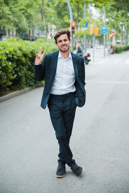 Successful smiling young businessman standing on street showing victory sign Free Photo
