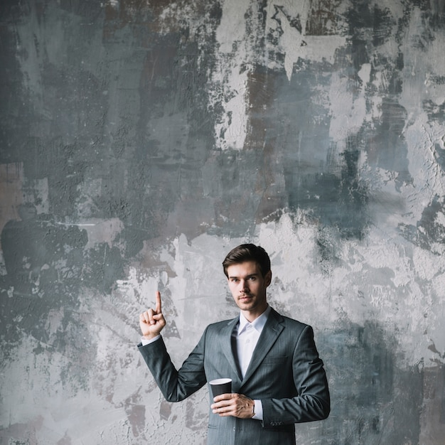 Successful young businessman standing against concrete wall holding cup of coffee pointing his finger upward Free Photo
