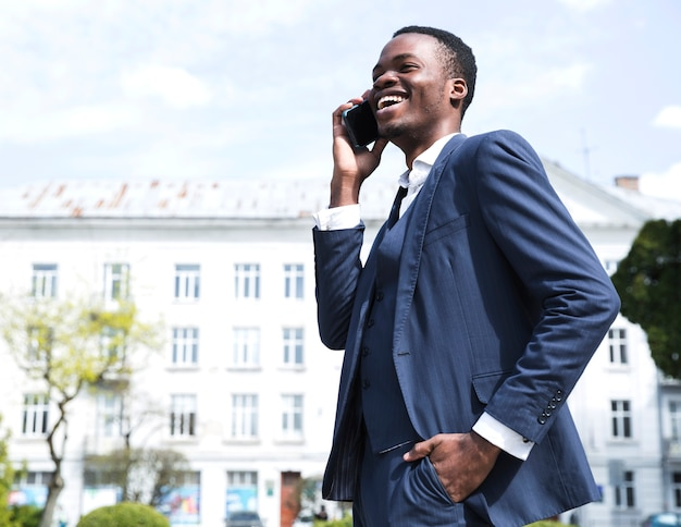 Successful young businessman with hands in his pocket talking on mobile phone Free Photo