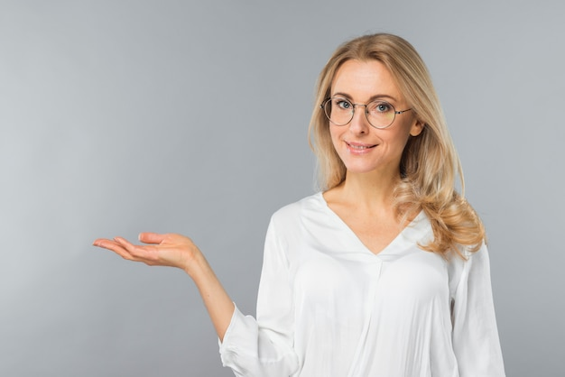 Successful young businesswoman wearing eyeglasses presenting against gray backdrop Free Photo