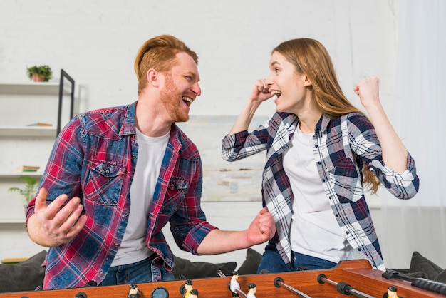 Successful young couple enjoying playing the table soccer game at home Free Photo