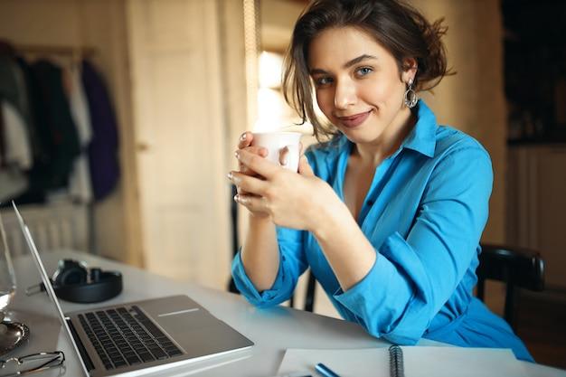 노트북 앞에 앉아, 컵을 들고, 커피를 즐기고, 온라인 수업을 준비하고, 먼 일을 즐기는 접착제 드레스에 성공적인 젊은 여성 교사. 휴대용 컴퓨터를 사용 하여 예쁜 학생 소녀 무료 사진