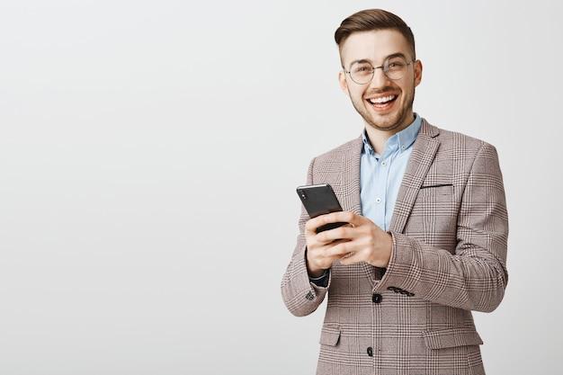 Sms di successo giovane imprenditore maschio, messaggistica con lo smartphone Foto Gratuite