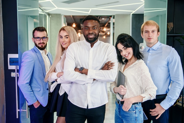 Premium Photo | Successful young multiracial work team of handsome men and  pretty women which looking at camera with sincerely smiles on the  background of the modern stylish office.