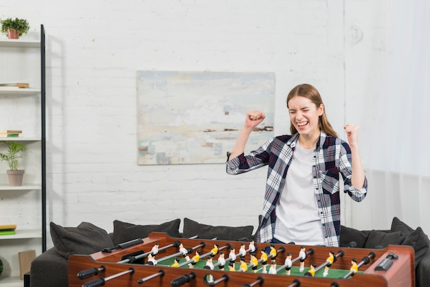 Successful young woman standing near the table soccer game clenching her fist Free Photo