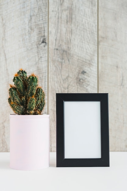Succulent plant in container near the blank picture frame on desk against wooden wall Free Photo