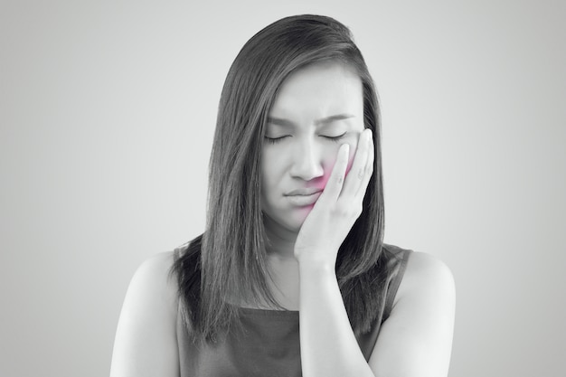 Suffering from a toothache, asian woman wearing a red shirt suffering Premium Photo