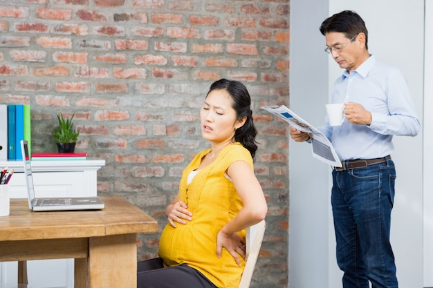 Suffering pregnant woman sitting on chair at home while husband reading newspaper Premium Photo