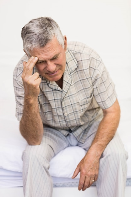 Suffering senior man touching his forehead at home Premium Photo