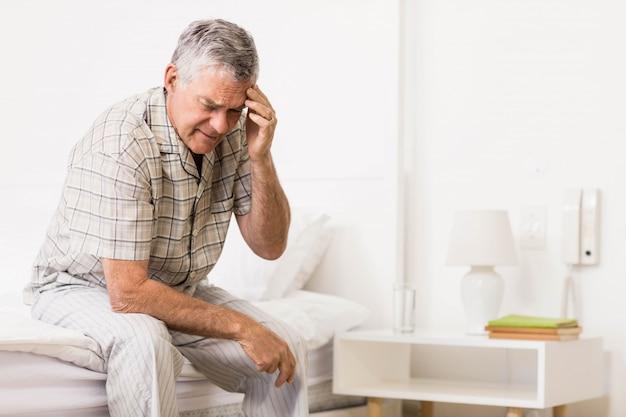 Suffering senior man touching his forehead at home Premium Photo