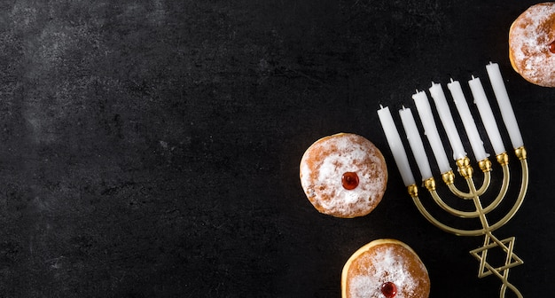 ユダヤ人のハヌカ本枝の燭台と黒、パノラマビューのsufganiyotドーナツ Premium写真