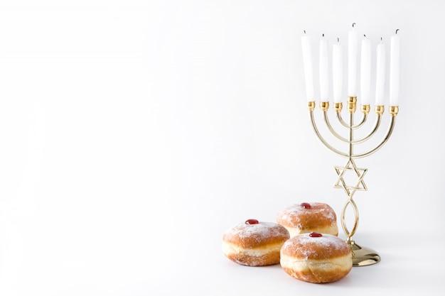 ユダヤ人のハヌカ本枝の燭台と分離されたsufganiyotドーナツコピースペース Premium写真