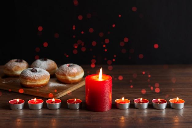 キャンドル(伝統的な燭台)とハヌカのお祝いの木製テーブルに伝統的なドーナツsufganiyotの本枝の燭台。 Premium写真