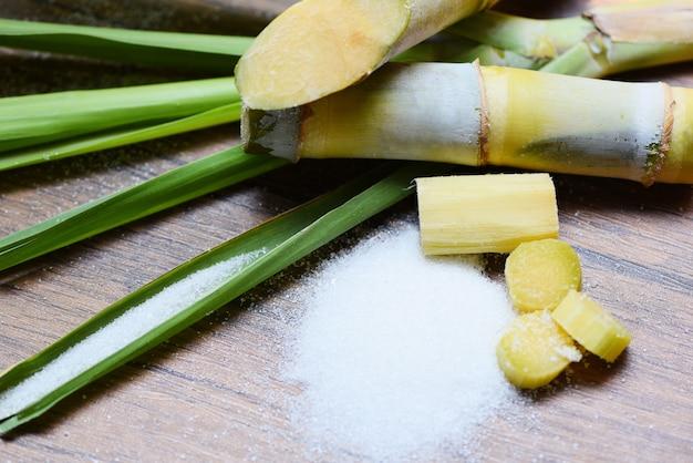 Sugar cane and white sugar on table Premium Photo
