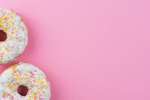 Sugar donuts with chocolate glaze and sprinkles on pink background Free Photo
