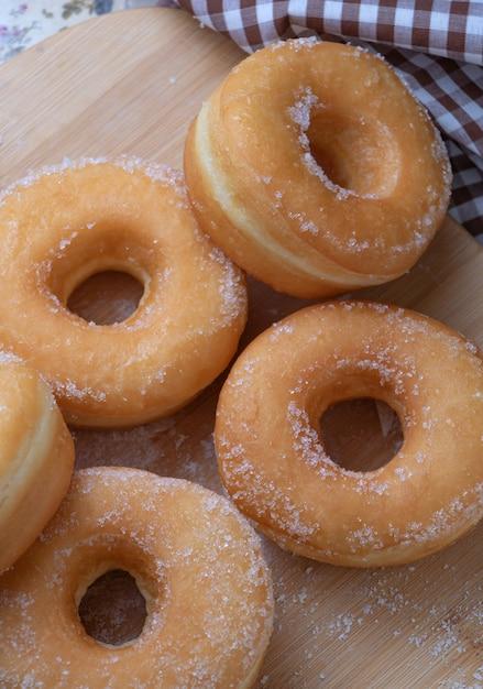 Sugar donuts on wooden board Premium Photo