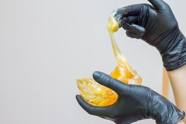 Sugar paste or wax honey for hair removing with black gloves hands  - depilation and beaut Premium Photo