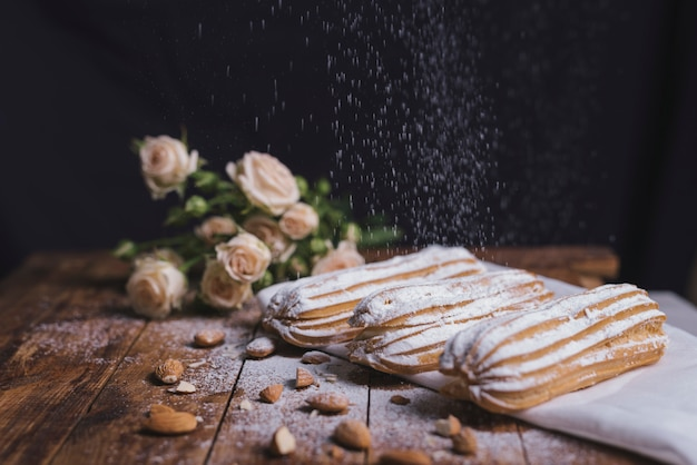 Sugar powder dusted on baked eclairs with almonds on wooden backdrop Free Photo