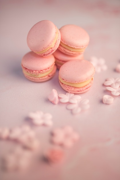 Sugar powder dusted on blue macaroons with merengue on black textured background Free Photo
