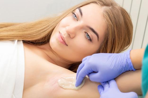 砂糖漬け:脇の下での液糖による脱毛。女性のための脱毛手順を作る砂糖漬けのマスター。糖液ペーストによる脱毛。 Premium写真