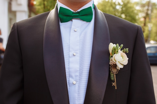 b4d4bf3caf4c Suit of groom with green bow tie and boutonniere Photo | Free Download