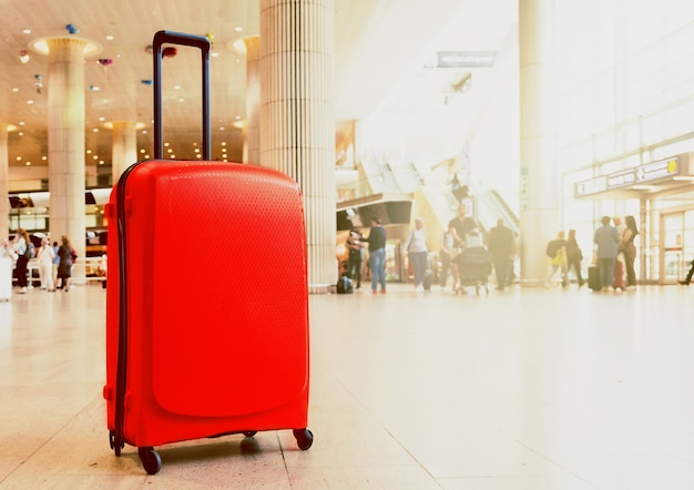 Suitcase in airport airport terminal waiting area with lounge zone as a background. vacation theme concept. Premium Photo