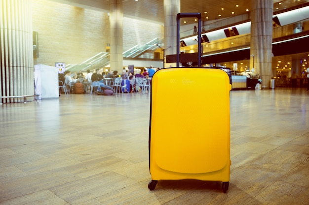 Suitcase in airport airport terminal waiting area with lounge zone as a background. vacation theme concept Premium Photo