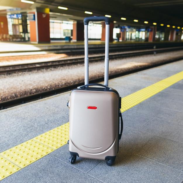 Suitcase on the platform of the railway station Premium Photo