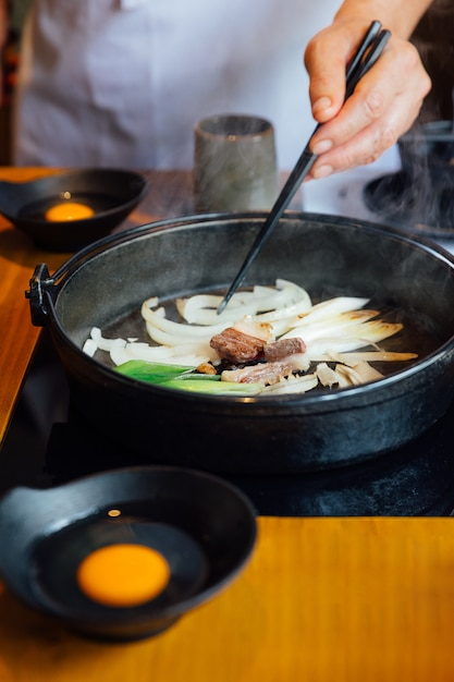 Шеф-повар жареный лук, лук-шалот и грибы в горячий горшок sukiyaki. Premium Фотографии