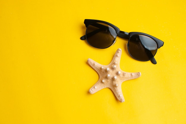 Summer accessories, sea shell and sun glasses. summer vacation and sea concept. Premium Photo