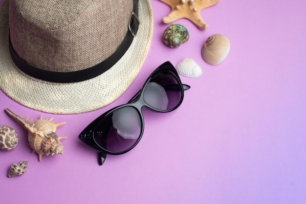 Summer accessories, shells, hat and sun glasses on pink background. summer vacation and sea concept. Premium Photo