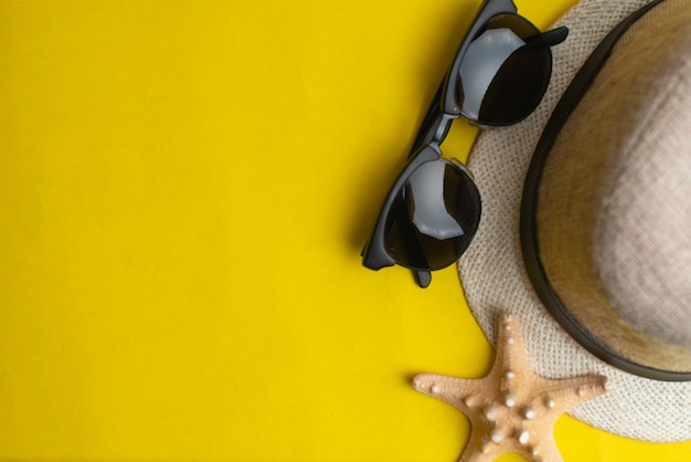 Summer accessories, shells, hat and sun glasses on yellow background. summer and sea concept. Premium Photo